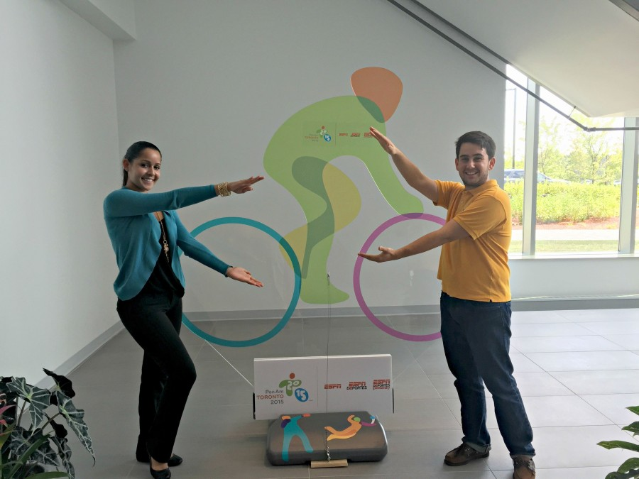 """Eneisy Rodriguez and Miguel Machado doing the Florida Gator """"chomp"""" in front of a Pan Am Games sign on ESPN's Bristol, Conn. campus. (Kyle Van Fechtmann/ESPN)"""
